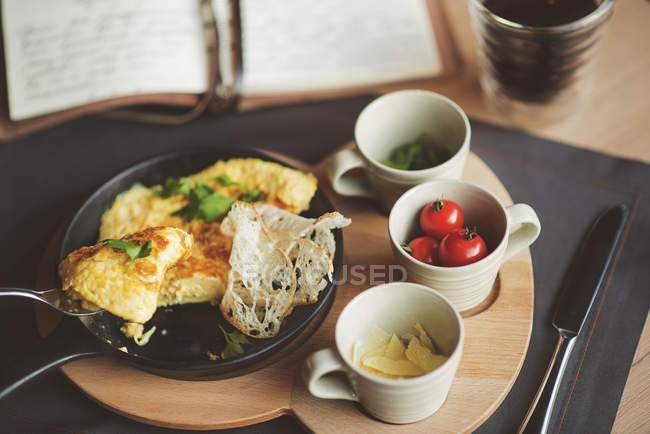 Omelett auf Pfanne mit frischen Kirschtomaten und Parmesan in Tassen — Stockfoto