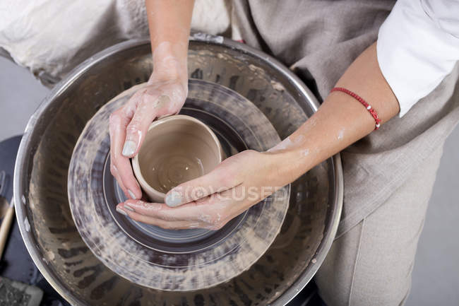 Close-up view of female potter hands making pot — Stock Photo