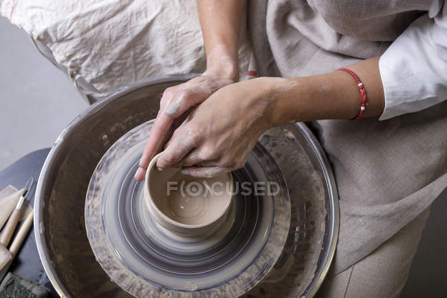 Крупный план женских рук гончаров, делающих горшок — стоковое фото