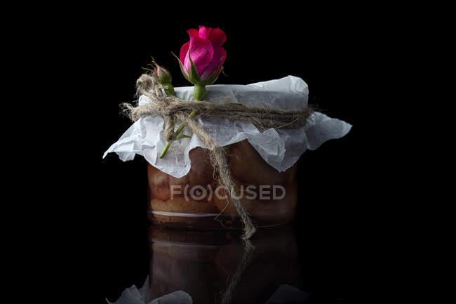 Pot de fruits en conserve avec décoration de fleurs roses — Photo de stock