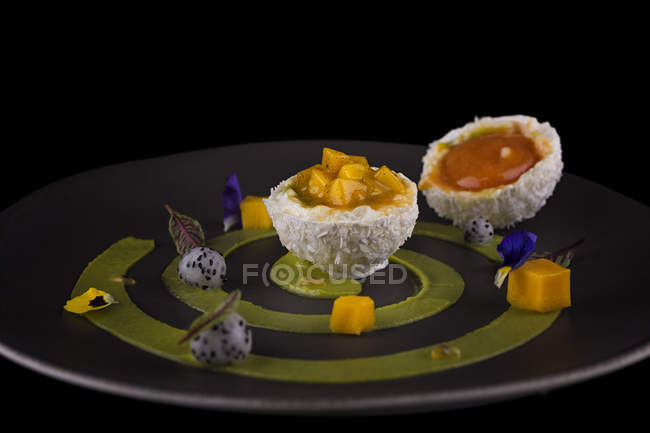 Coconut dessert with fruit filling served on grey plate — Stock Photo
