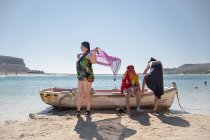 Tourists resting by old rowing boat on shore of Crete, Greece. — Stock Photo