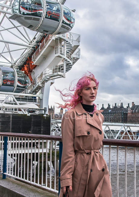LONDON, ENGLAND - CIRCA JANUARY, 2018: Pink-haired woman walking on embankment in front of London Eye. — Stock Photo