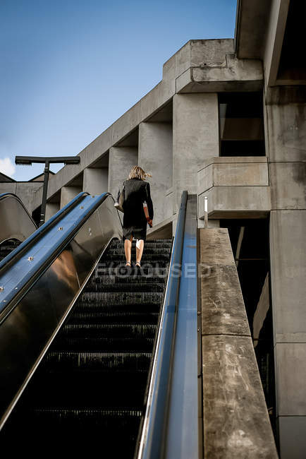 Rear view of woman lifting on street escalator in Miami, USA — Stock Photo