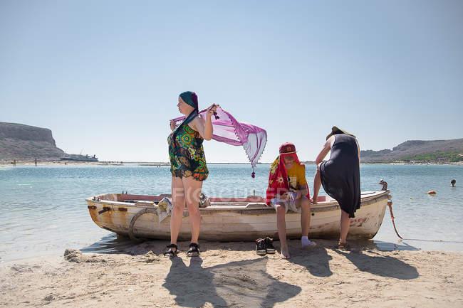 Los turistas descansando por remo antiguo barco en la costa de Creta, Grecia. - foto de stock
