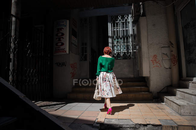 BELGRADE, SERBIA - CIRCA MAY, 15: Rear view of redhead woman in front of shabby building entrance. — Stock Photo
