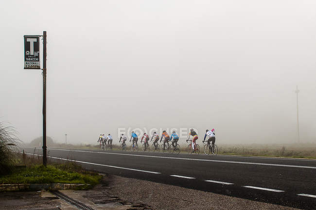 Group of cyclists on road beside misty field — Stock Photo
