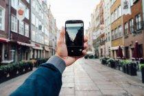 Main masculine tenant smartphone sur fond de paysage urbain flou — Photo de stock