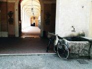 Bicicleta estacionada no fontanário em fundo de construção de passagem em arco — Fotografia de Stock