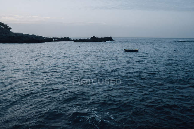 Seascape of coastal cliffs and floating empty boat in dusk — Stock Photo