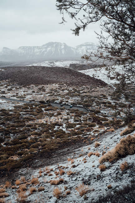 Valle erbosa coperta di neve, catena montuosa sullo sfondo — Foto stock