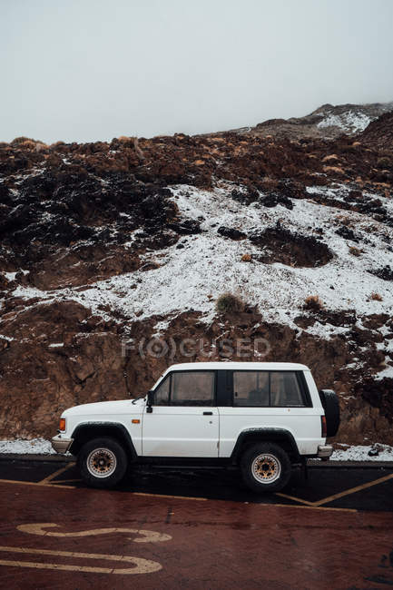 Side view of off-road car parked at roadside on background of snow-covered cliffs — Stock Photo