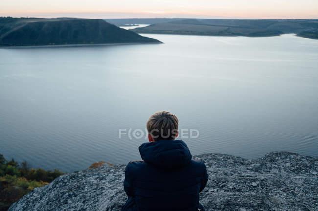 Young man on mountain top near calm river — Stock Photo