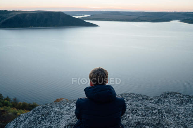 Young man on mountain top near calm river — Stock Photo