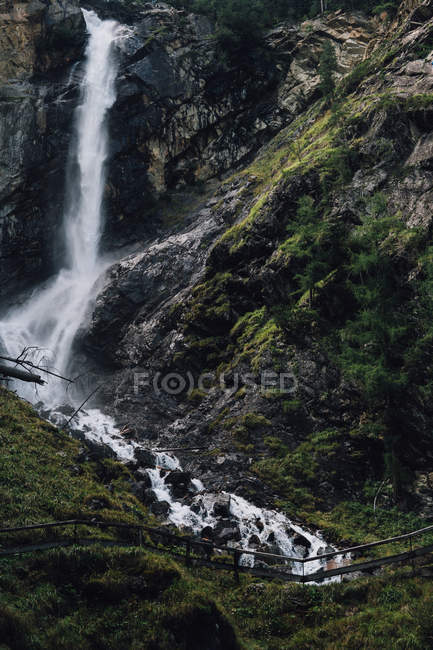 Scenic view to waterfall stream at green cliffs — Stock Photo