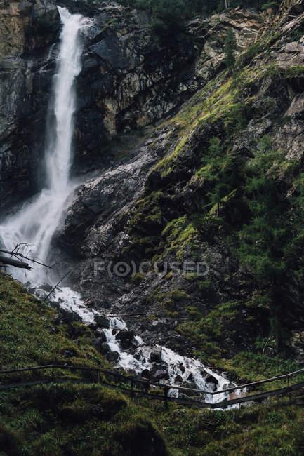 Живописный вид поток водопада на зеленые скалы — стоковое фото