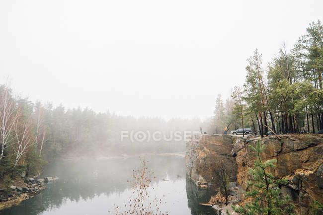 Paesaggio del fiume foresta nebbiosa con fuoristrada parcheggiata sulla scogliera — Foto stock