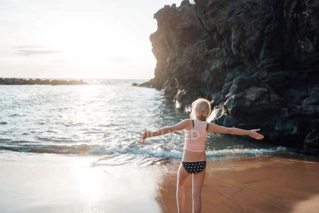 Junge Frau mit ausgestreckten Armen auf sandige Meeresufer stehend — Stockfoto