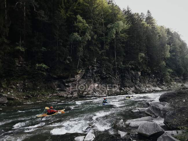 Kayaks swimming on forest river — Stock Photo