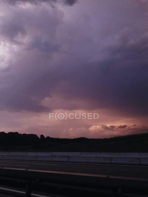 Scenic sunset cloudscape above countryside view and highway — Stock Photo