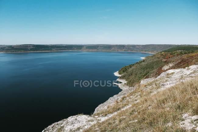 Serene landscape of lake shore slopes on sunny day — Stock Photo