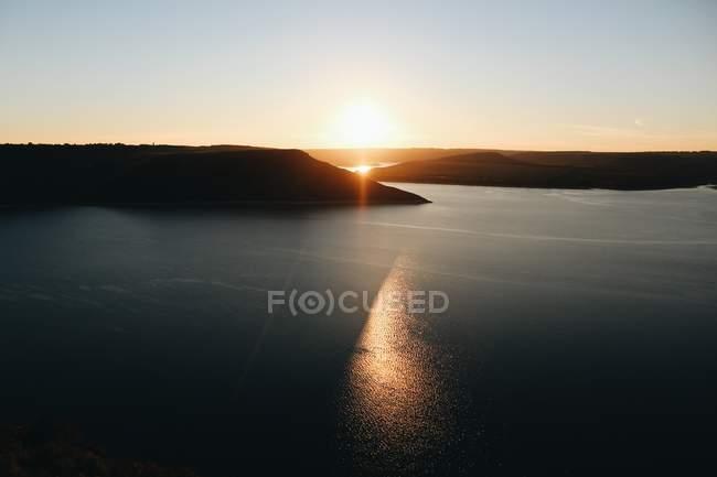 Paesaggio sereno di ampio fiume e shore piste nella luce del tramonto — Foto stock