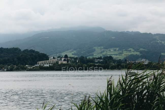 Tranquill paisagem do rio e enevoada costa verde — Fotografia de Stock