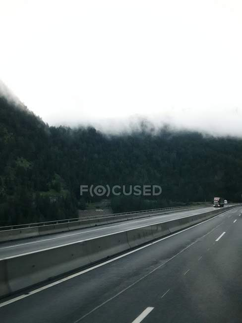 Ver os à estrada de tráfego na paisagem enevoada — Fotografia de Stock