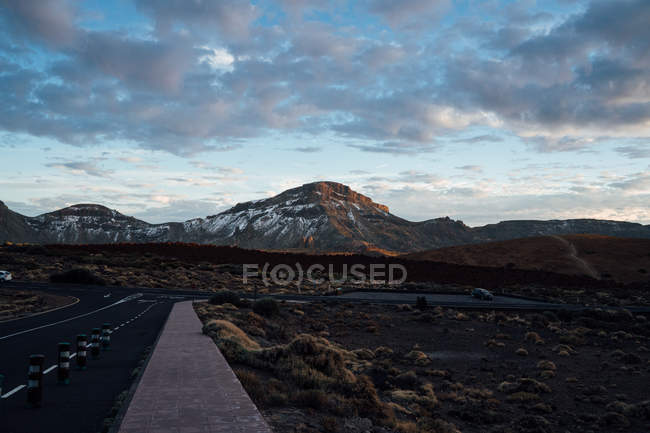 Panorama of road at mountain valley and serene cloudscape — Stock Photo
