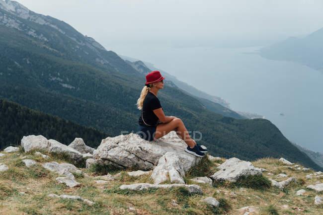 Seitenansicht der blonde Frau sitzt auf Boulder auf Hintergrund der Berghang und Himmel — Stockfoto