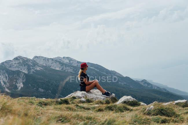 Seitenansicht der blonde Frau auf Boulder auf Hintergrund der Berghang und Wolkengebilde sitzend — Stockfoto