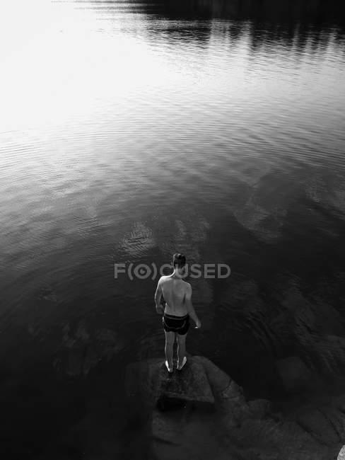 Vista trasera del hombre de pie en la roca en medio del río en el día soleado - foto de stock