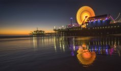 Ferris wheel and Santa Monica Pacific park lights reflected in water surface — Stock Photo