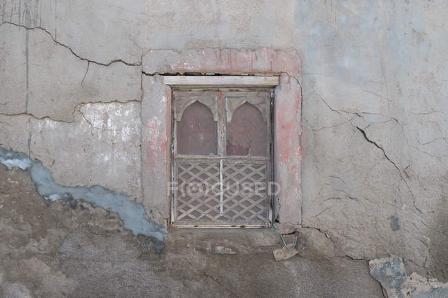 A crumbling old wall with delicately carved, arched window frames with faded paint in Dhofar, Oman. — Stock Photo