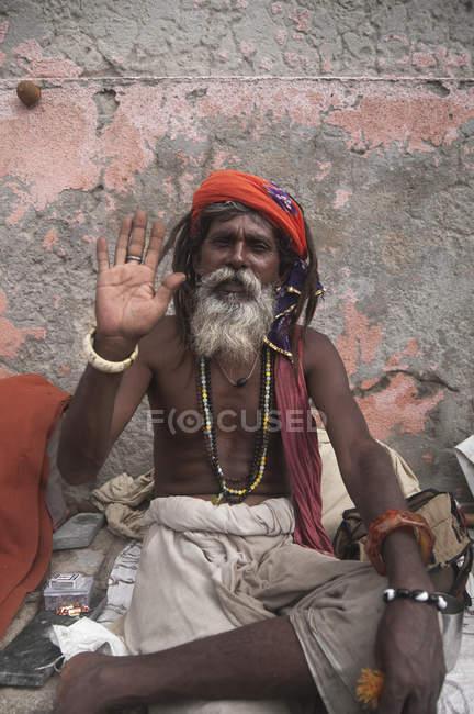 Saddhu в Дварка сидячи вивітрювання стіни, Гуджарат, Індія — стокове фото