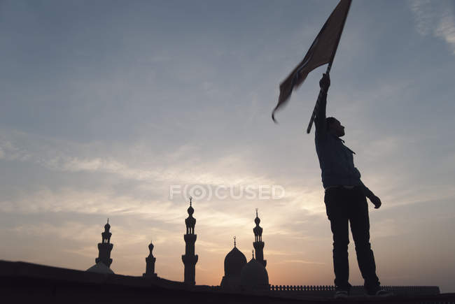 Bird Man in Islamic Cairo waving flag to signal his pigeons to return to tower — Stock Photo
