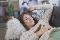 Молодая женщина отдыхает на диване и держит книгу — стоковое фото