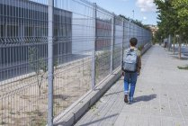 Rear view of schoolboy with backpack walking near fence at urban street — Stock Photo
