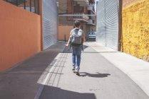 Rear view of schoolboy with backpack walking on urban street at daytime — Stock Photo