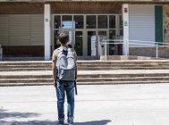 Visão traseira do estudante de pé e olhando para o prédio da escola — Fotografia de Stock