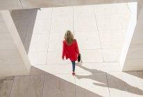 Vue aérienne de femme en manteau rouge, marche en ville — Photo de stock