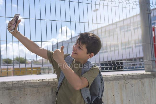 Студент делает селфи и показывает большой палец перед камерой на улице — стоковое фото