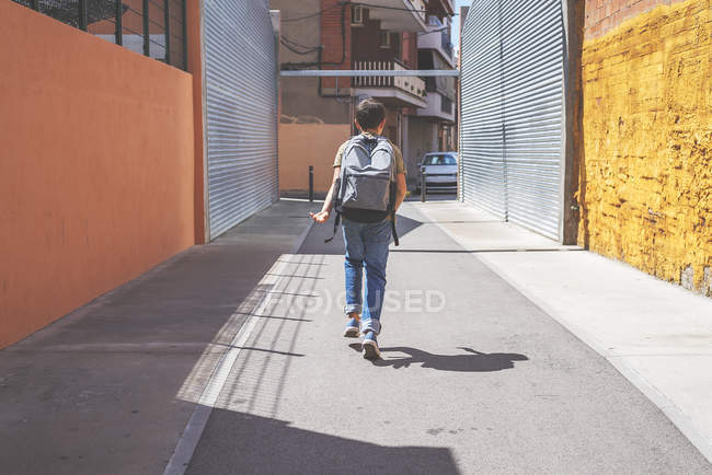 Вид сзади на школьника с рюкзаком прогуливающимся по городской улице днем — стоковое фото