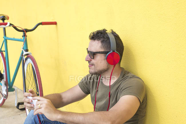 Portrait of man sitting on floor using smartphone and listening music in headphones — Stock Photo