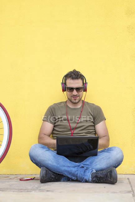 Bonito homem digitando no laptop em fones de ouvido enquanto sentado perto da parede amarela — Fotografia de Stock