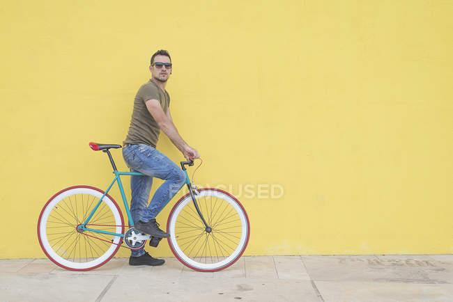 Side view of young adult man with vintage bicycle near yellow wall — Stock Photo