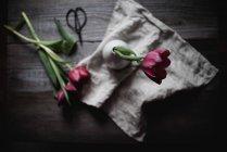 Vista superior de tulipán recién cortado en jarrón sobre mesa rústica - foto de stock