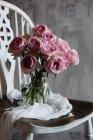 Blumenstrauß rosa rose in Glaskanne auf Vintage Sessel — Stockfoto