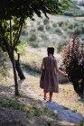 Rear view of girl walking down on hillside in park. — Stock Photo