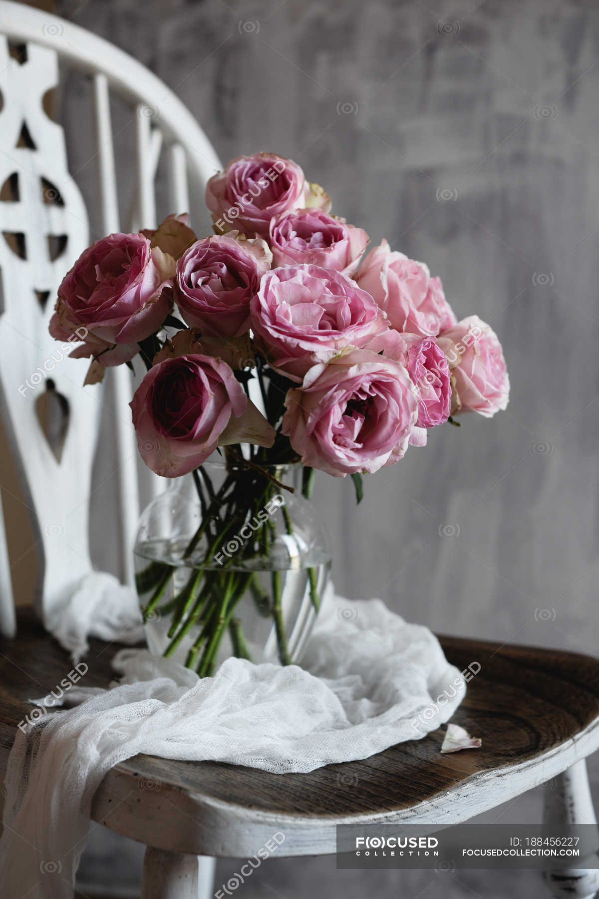 Bunch Of Pink Rose Flowers In Glass Jug On Vintage Chair Still